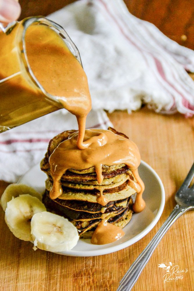 nut butter syrup pouring over baby banana pancakes from raiasrecipes.com