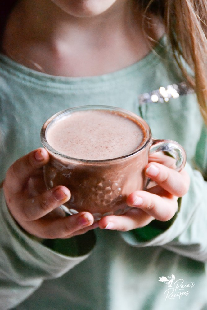 girl holding cup of nourishing spiced hot cocoa from raiasrecipes.com