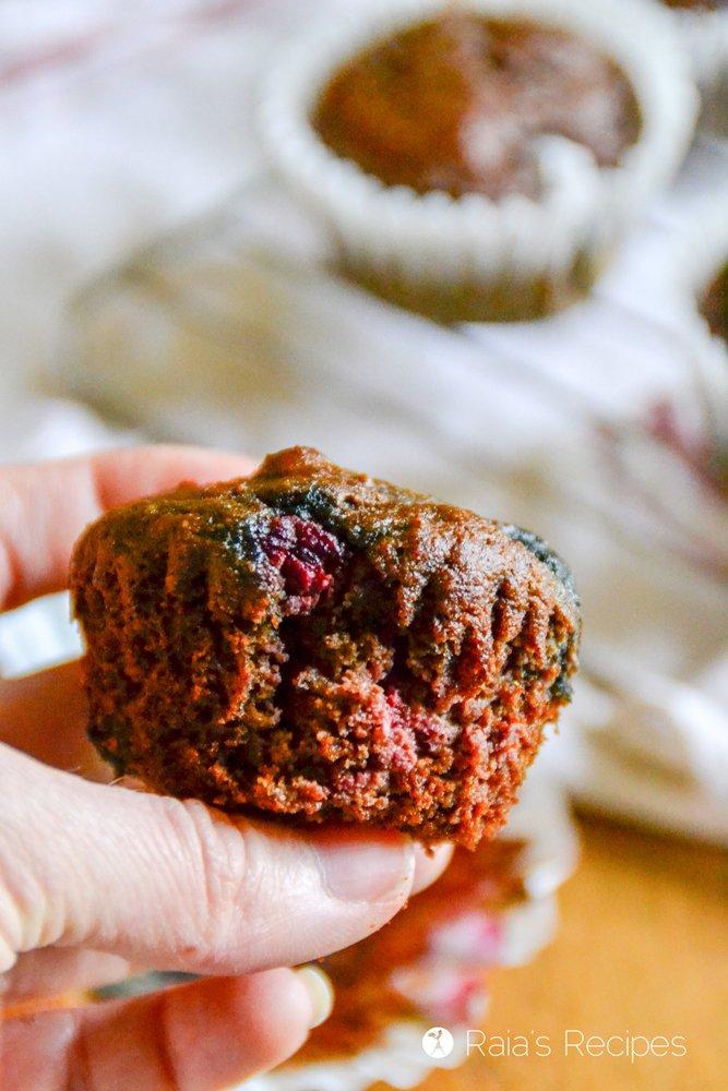Holding a dark chocolate triple berry muffin raiasrecipes.com