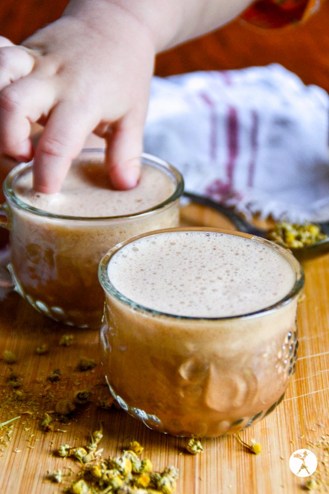 Little fingers in a glass mug of chocolate chamomile moon milk from raiasrecipes.com